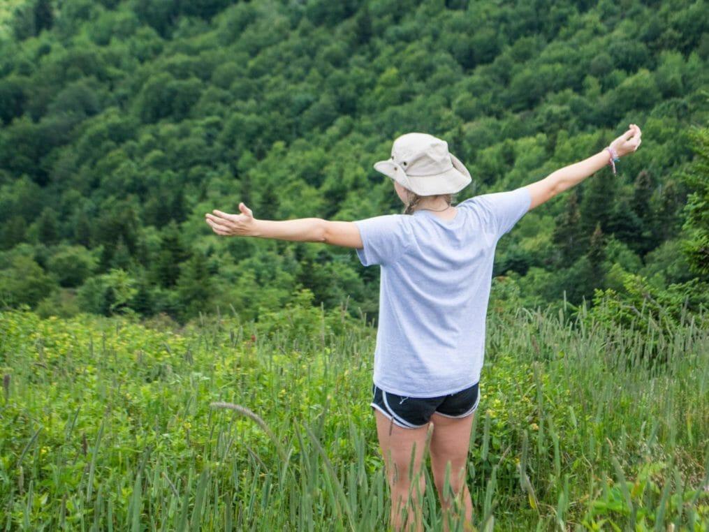 Camper with arms wide open by mountains at the Hendersonville Adventure Day Camp