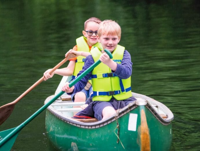 Two boys canoeing on the lake
