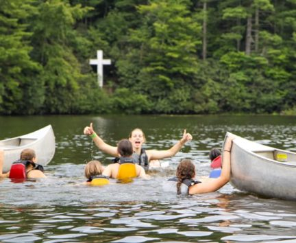 Staff and campers swimming by canoes on the Rock Climbing & Canoeing Pioneer Expedition