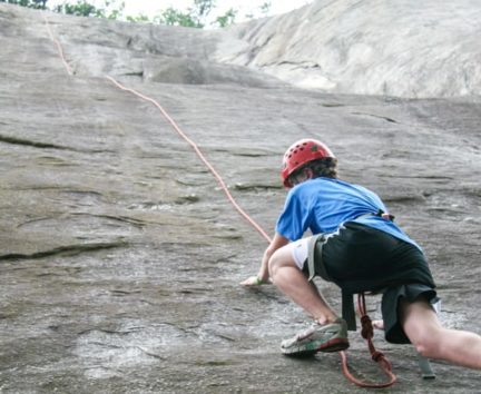 Boy climbing a rock wall on the Rock Climbing & Canoeing Pioneer Expedition