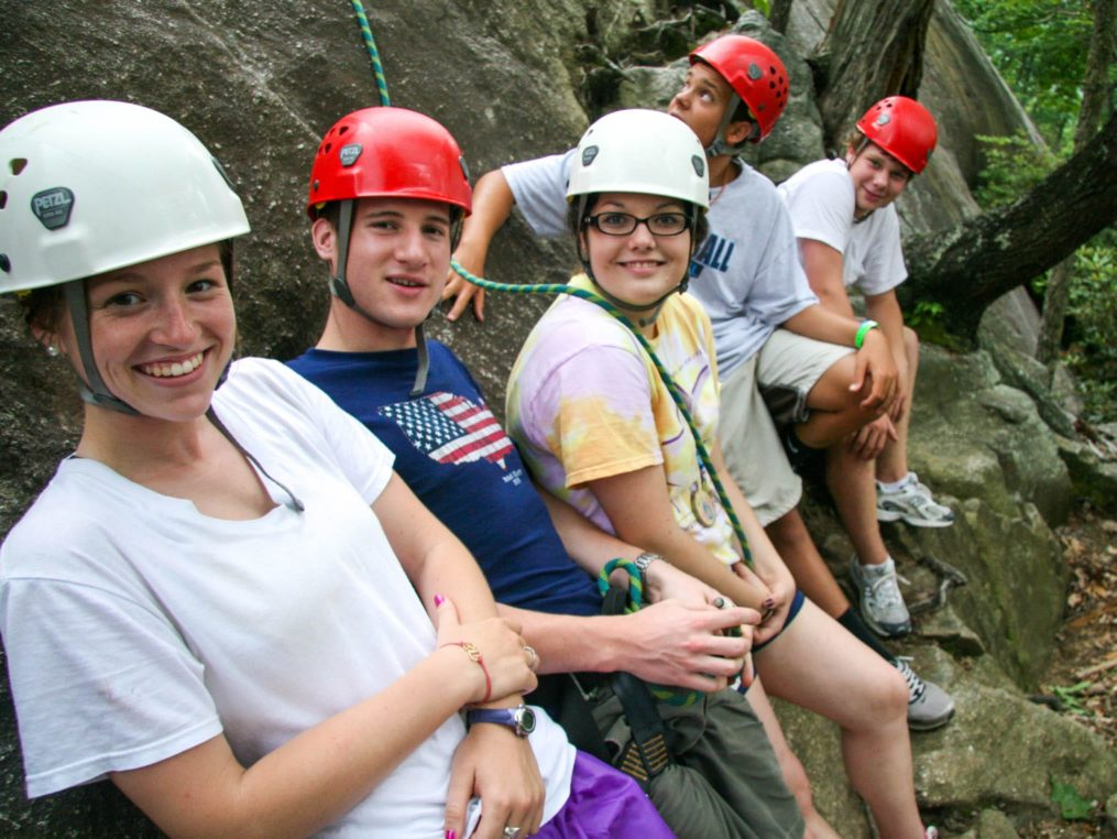 Group of teen climbers standing by rock wall on the Rock Climbing & Canoeing Pioneer Expedition