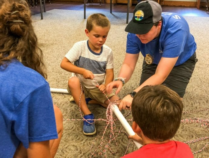 Leadership Academy campers with younger campers building paper structures