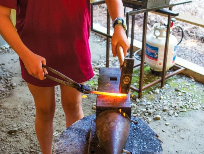 Camper at blacksmithing activity