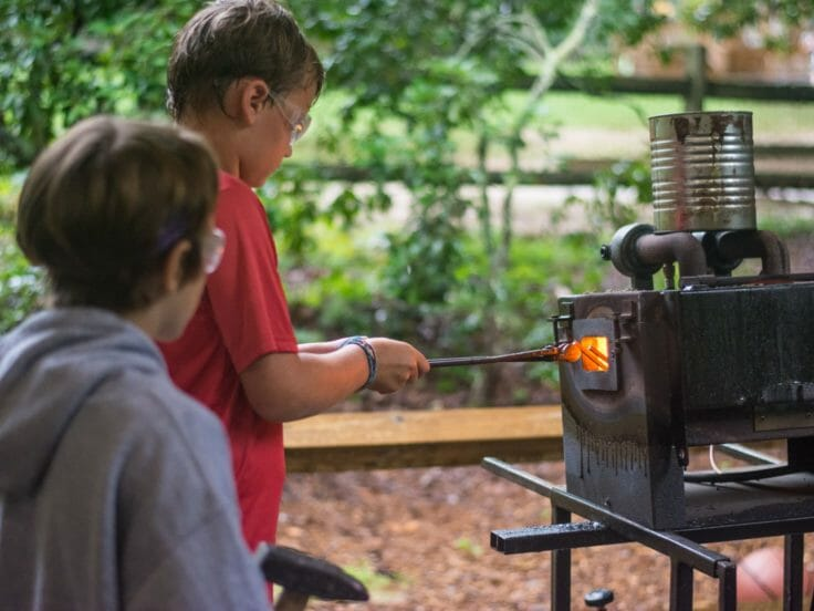 Campers blacksmithing at Hendersonville Day Camp