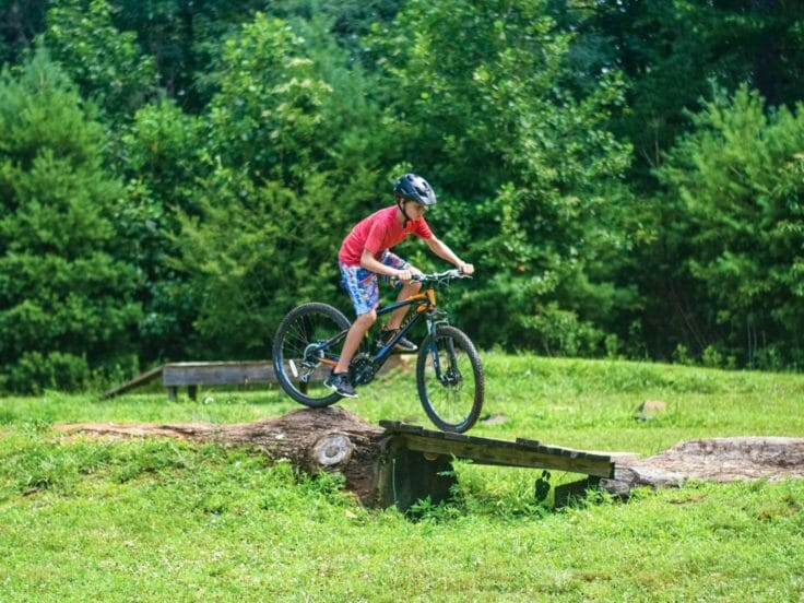Camper biking over obstacle at the Hendersonville Adventure Day Camp