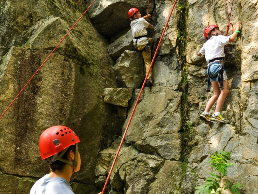 Two young male climbers on an outdoor rock wall on the Rock Climbing & Canoeing Pioneer Expedition