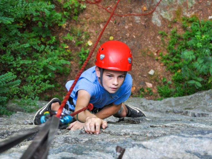Young male climber reaching for hold on a rock wall on the Rock Climbing & Canoeing Pioneer Expedition