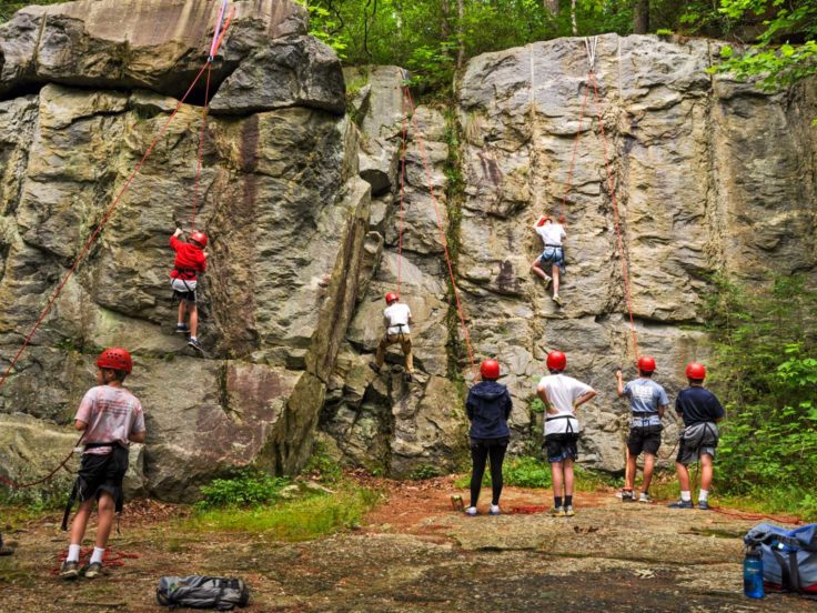 Group of teens climbing a rock wall on the Rock Climbing & Canoeing Pioneer Expedition