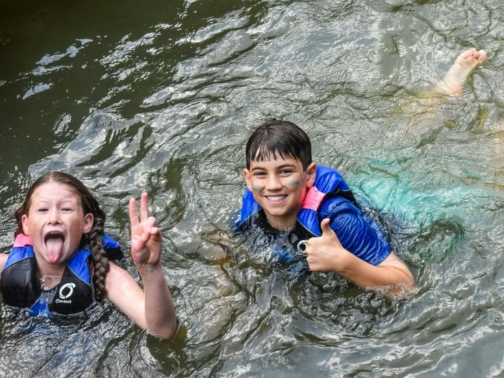 Two campers swimming and giving a thumbs up