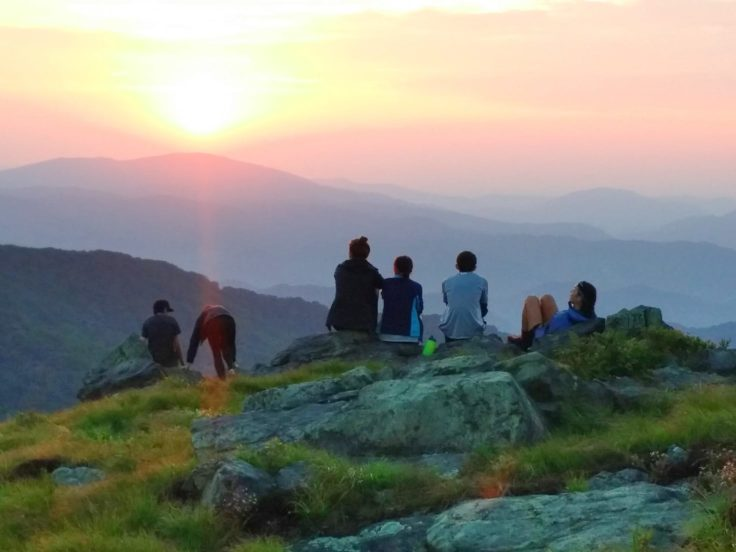 Campers sitting on a mountain, looking out at the sunset