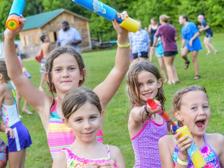 Girl with water guns and wearing bathing suits at Hendersonville Day Camp