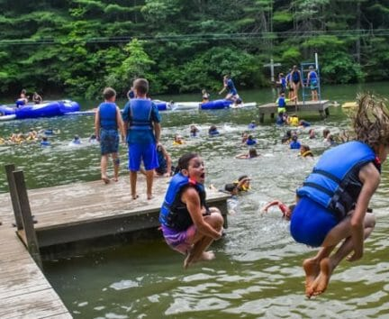 Campers jumping into lake from dock at Hendersonville Day Camp