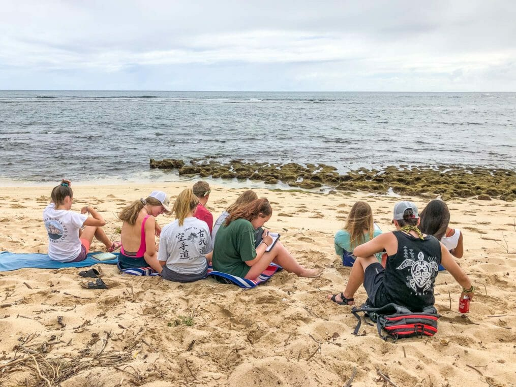 Explorers on the Hawaii Expedition writing on the beach