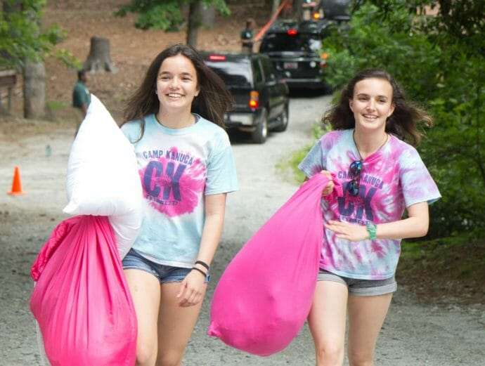 Two girls walking to camp with packed bags