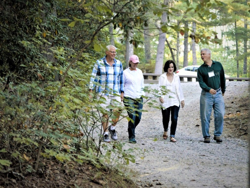 Four adults walking at camp